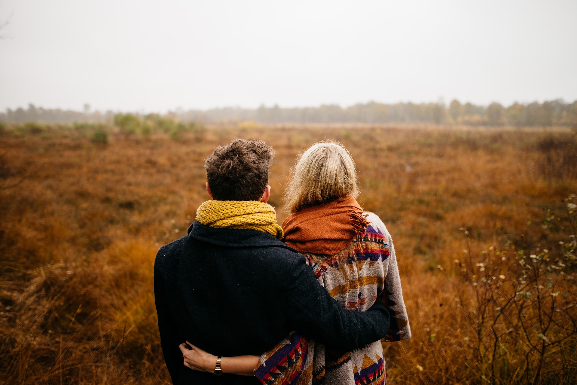 A couple are embracing. They look over a grassy field.